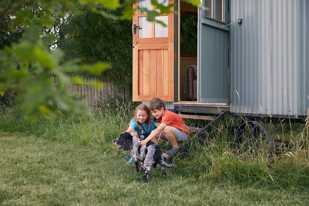 children sitting on step of shepherd's hut with a dog