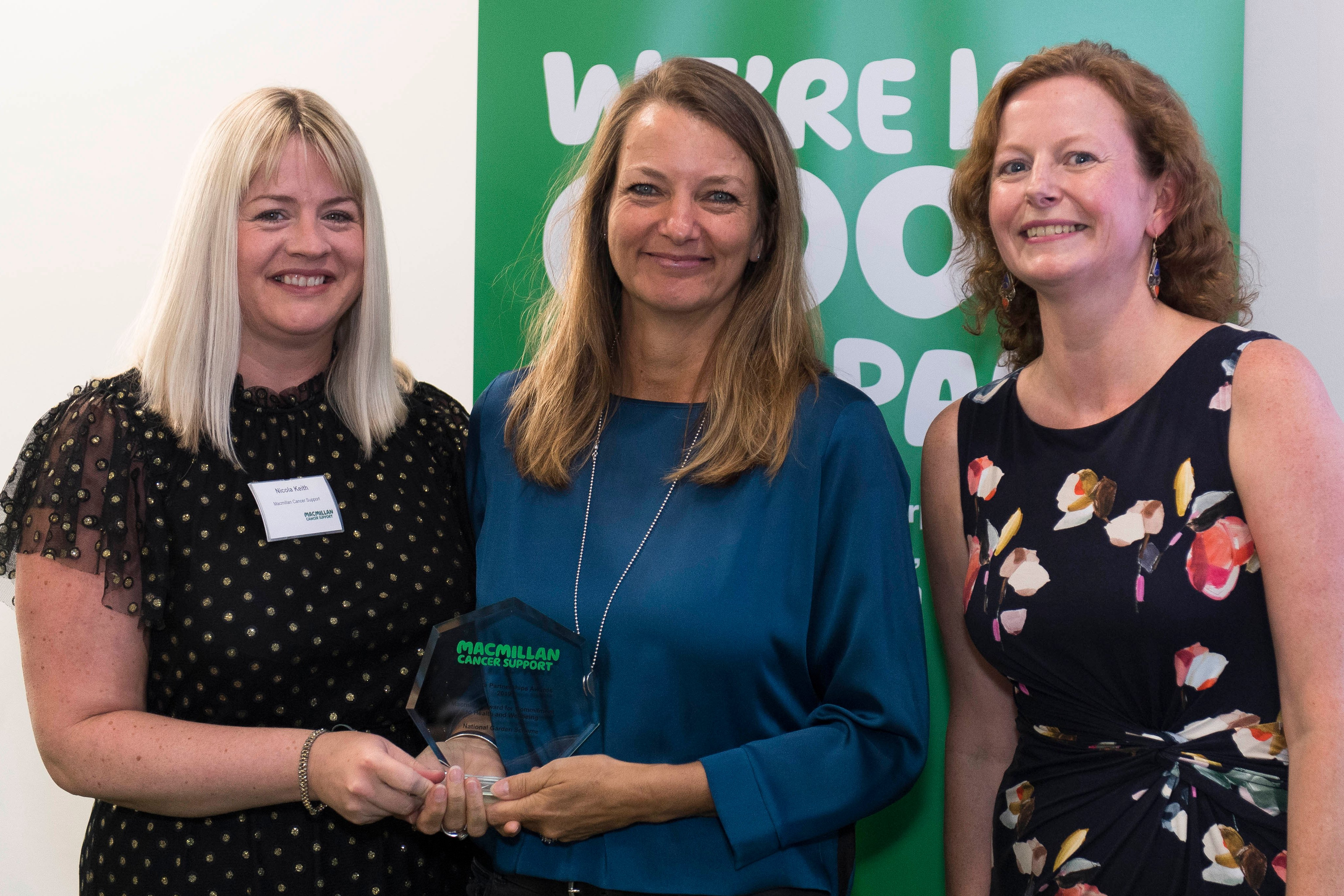 Macmillan Cancer Support's Nicola Keith (left) and Natasha Parker (right) present the award for Commitment to Health and Wellbeing to Vicky Flynn
