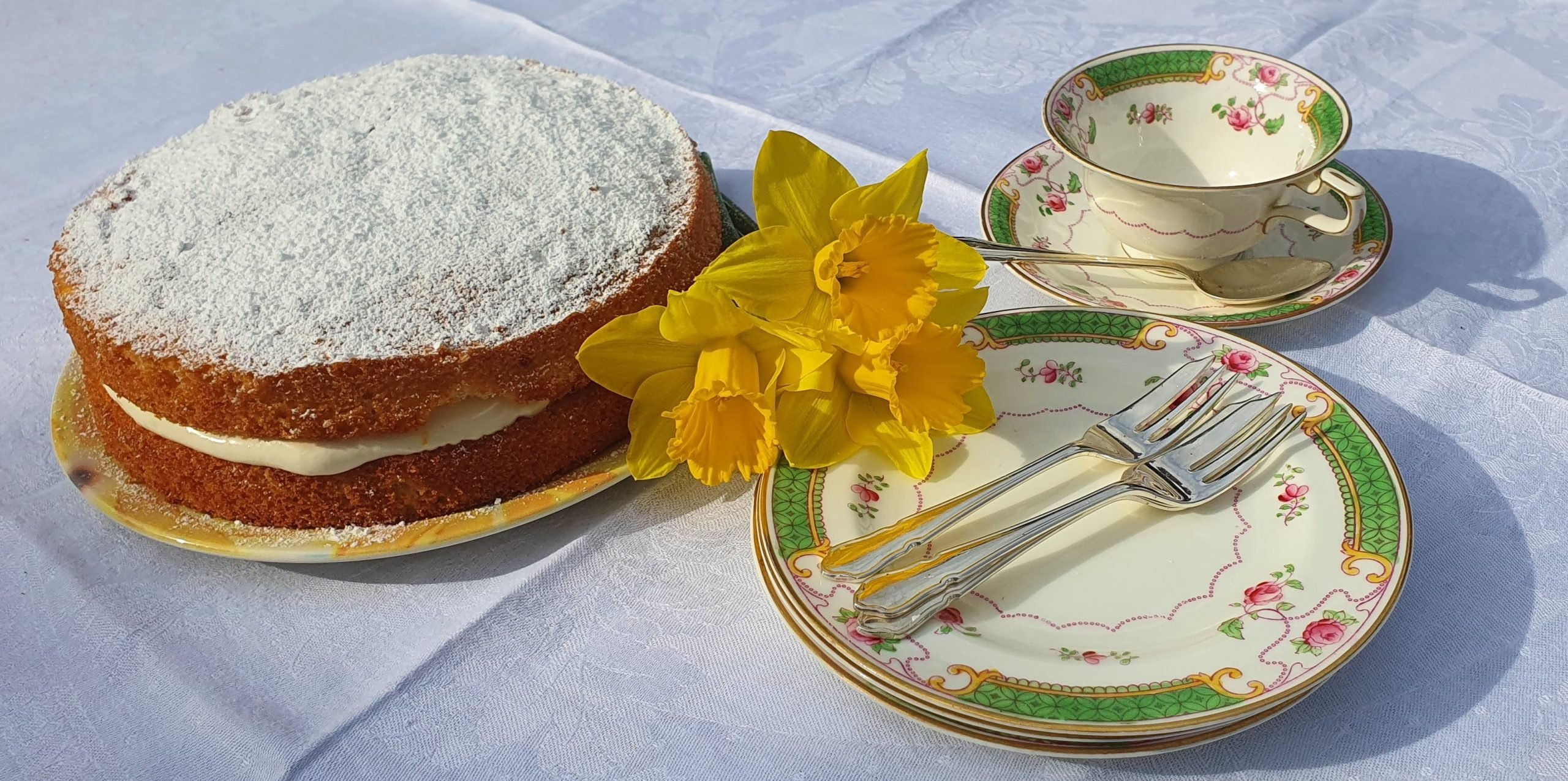 Lemon cake decorated with a daffodil, with plates and cups beside it